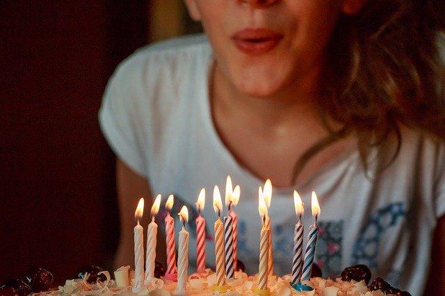 fille qui souffle les bougies de son gateau d'anniversaire